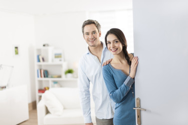 Cheerful couple inviting people to enter in home